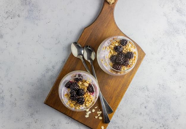 Yogurt con granola, semillas de chia y moras sobre un fondo gris. desayuno. alimentación saludable.