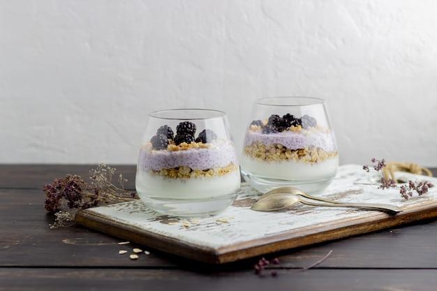 Yogurt con granola, semillas de chia y moras sobre un fondo de madera.