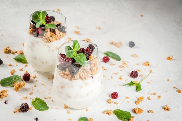 Yogurt y granola con vasos de fruta fresca