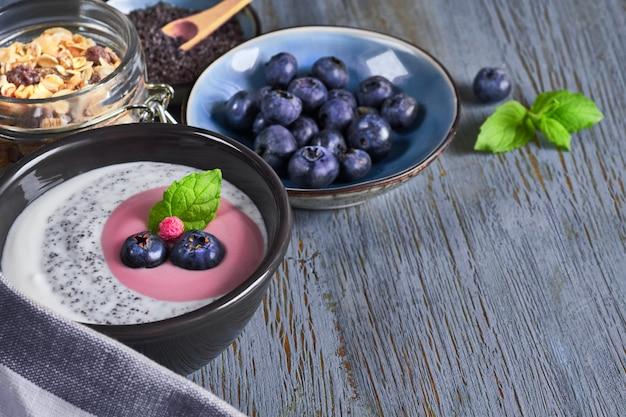Yogurt con muesli y arándanos con menta, postre saludable en madera