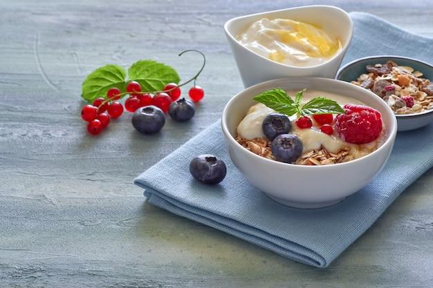 Yogurt con muesli y bayas, postre saludable sobre fondo neutro