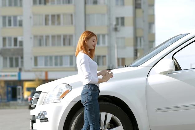 Yong mujer bonita de pie cerca de un gran coche todo terreno al aire libre.