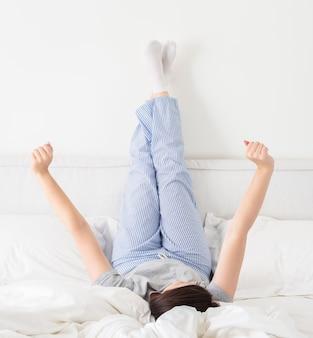 Yong mujer en la cama con las piernas en alto contra la pared