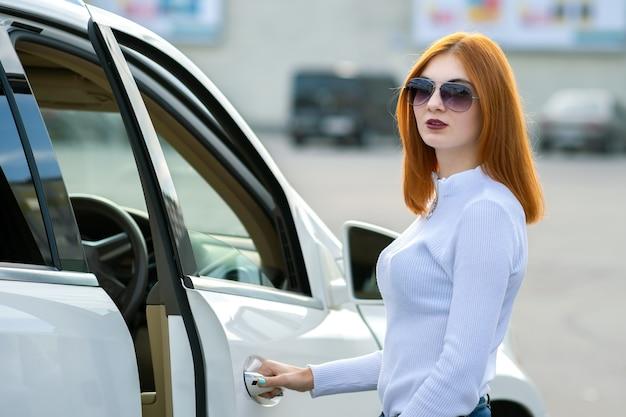 Yong pretty woman de pie cerca de un gran coche todo terreno al aire libre
