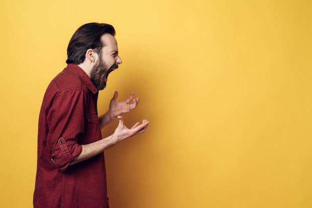 Youg barbudo gritando hombre enojado frustrado
