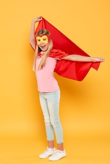 Yougn niña jugando superhéroe con disfraz