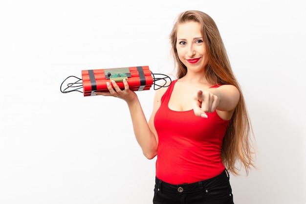 Yound mujer rubia apuntando a la cámara con una sonrisa satisfecha, segura y amigable, eligiéndote sosteniendo una bomba de dinamita