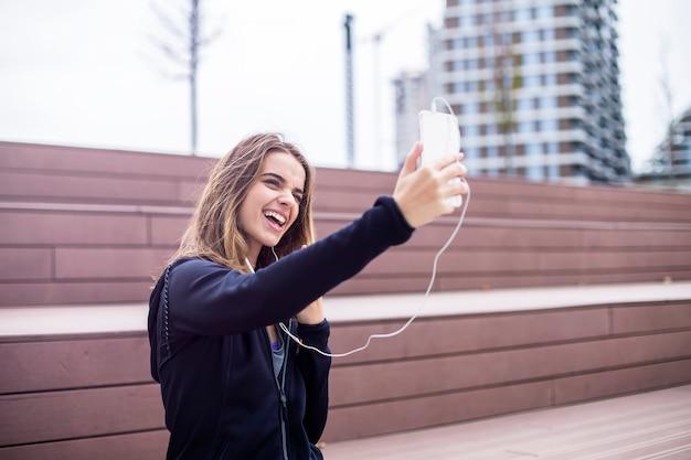 Young encaja mujer deportiva y escucha música y toma selfie en teléfono móvil y descansa después de entrenar