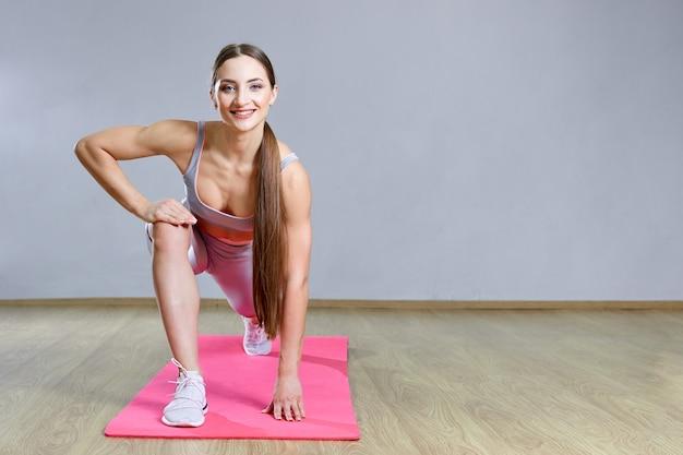 Young fit mujer haciendo ejercicio en un gimnasio. chica deportiva está entrenando cross fitness con colchoneta