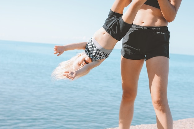 Young fit mujer mamá con linda niña haciendo ejercicio en la playa juntos