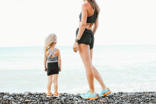 Young fit mujer mamá con linda niña haciendo ejercicio en la playa de la mañana juntos