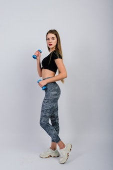 Young fit mujer con pesas sobre fondo gris