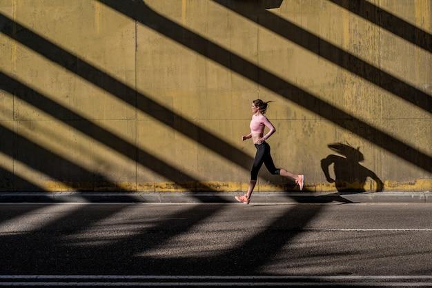 Young fit mujer rubia corriendo en la calle