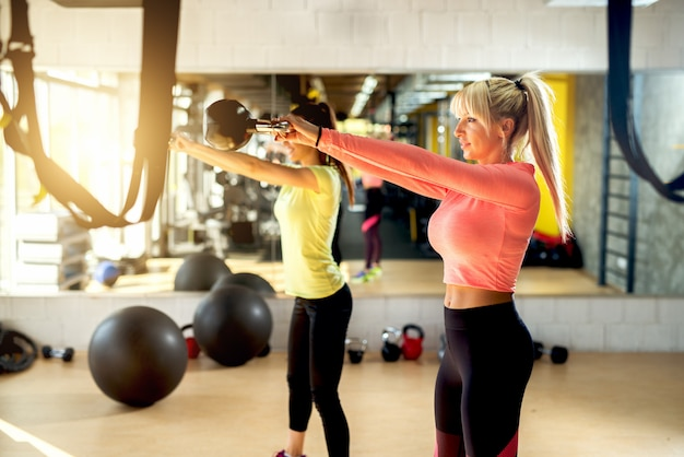Young fit women swing kettlebell con dos brazos