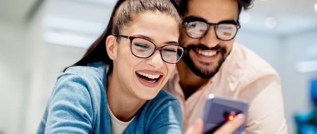 Young satisfecho elegante pareja encantadora probando el nuevo modelo de un teléfono