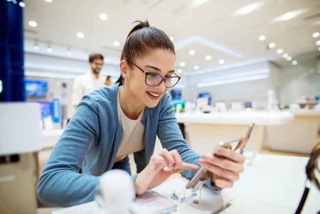 Young satisfizo a una chica hermosa, encantadora y elegante probando el nuevo modelo de un móvil desde el escritorio de la tienda de tecnología.