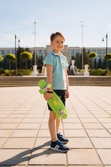 Young school cool boy en ropa brillante de pie con penny board en las manos