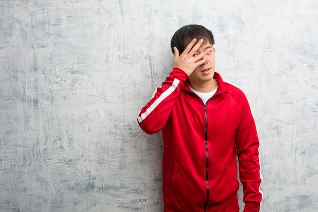 Young sport fitness chino avergonzado y riendo al mismo tiempo