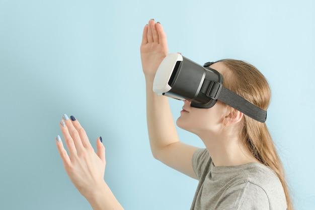 Yuong mujer con gafas de realidad virtual. fondo azul