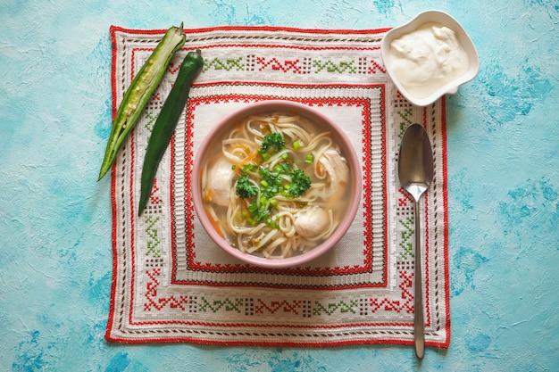 Zama, sopa de pollo rumano y moldavo con fideos. la sopa tradicional de resaca se sirve con pimiento picante y crema agria.