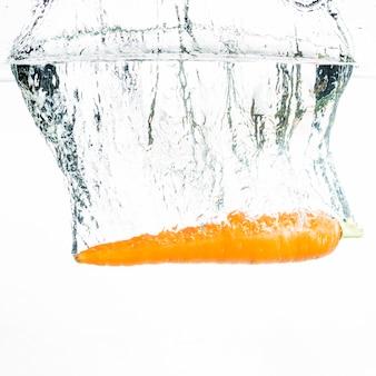 La zanahoria cae profundamente bajo el agua con una gran salpicadura