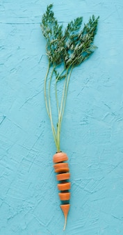 Zanahoria cortada en rodajas sobre fondo azul. endecha plana.