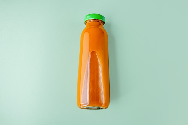 Zanahoria detox nutritiva o jugo de calabaza en botella de vidrio. concepto de dieta alcalina. bebida vegetariana orgánica sobre fondo verde