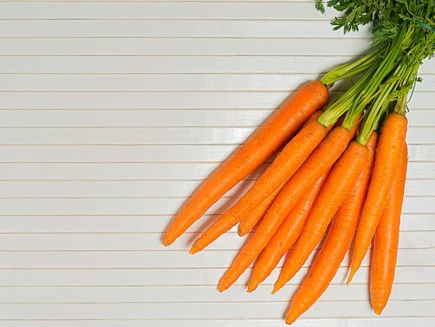 Zanahoria fresca y dulce en la mesa de madera blanca, vista superior