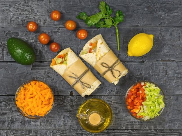 Zanahoria, pimiento, aguacate, tomates en pan de pita sobre una mesa rústica