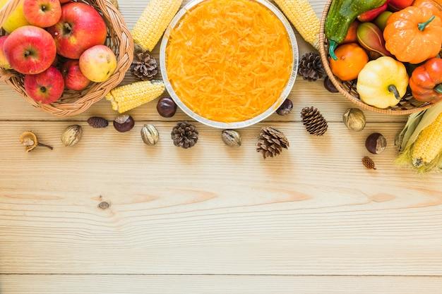 Zanahoria en plato entre frutas y verduras.