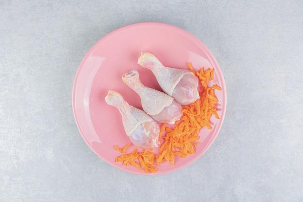 Zanahoria rallada y muslo de pollo en el plato, sobre la superficie de mármol