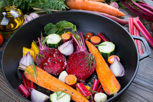 Zanahoria, remolacha, acelga, calabacín, cebolla, ajo, tomate en la sartén negra con aceite de oliva. surtido de verduras de la huerta. comida sana