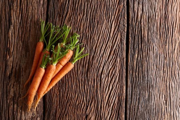 Zanahorias baby sobre fondo de madera con copyspace