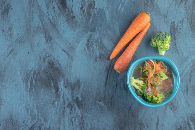 Zanahorias, brócoli y tazón de sopa de pollo, sobre fondo azul.
