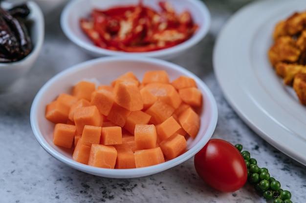 Las zanahorias se cortan en cubitos en una taza con tomates y semillas frescas de pimiento.