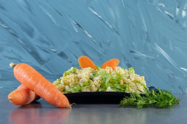 Zanahorias, eneldo y ensalada de capital en un plato, sobre fondo azul.