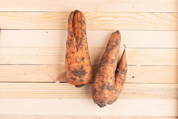 Zanahorias feas en mesa de madera