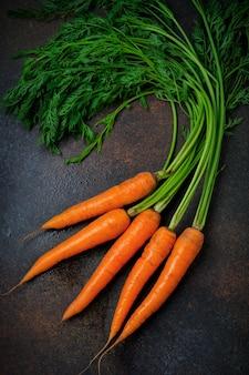 Zanahorias frescas crudas en mesa oscura. enfoque selectivo vista superior. copie el espacio concepto de comida vegetariana.
