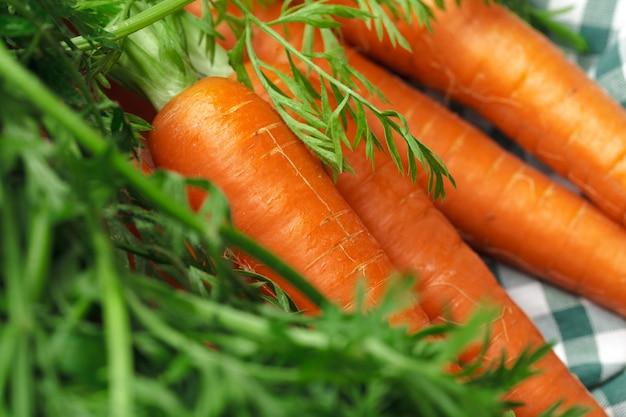 Zanahorias frescas sobre mantel a cuadros