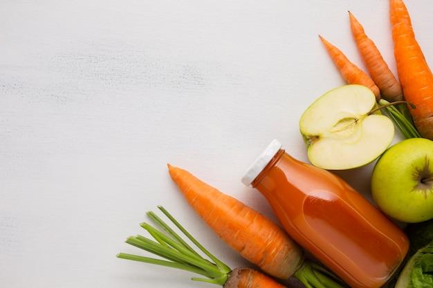 Zanahorias, manzanas y jugo con espacio de copia