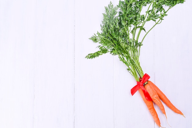 Zanahorias en una mesa de madera blanca