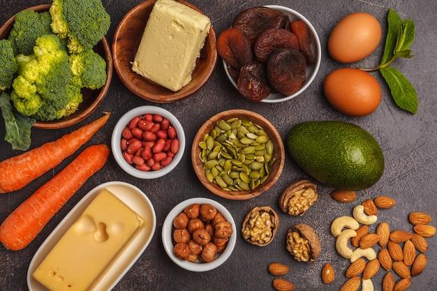 Zanahorias, nueces, brócoli, mantequilla, queso, aguacate, albaricoques, semillas, huevos. fondo oscuro, espacio de copia