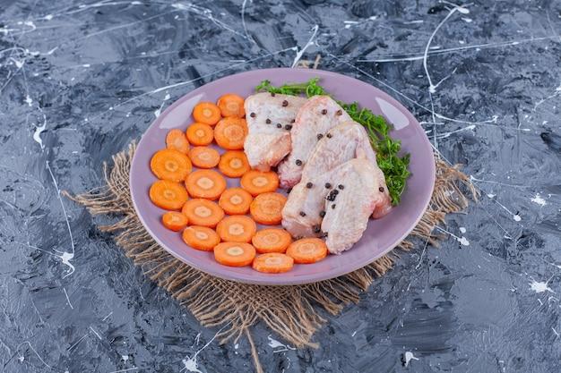 Zanahorias en rodajas, alas y verduras en un plato sobre una arpillera sobre la superficie azul