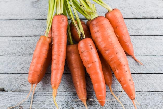 Zanahorias en la vista superior de fondo de madera