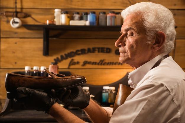 Zapatero concentrado en taller haciendo zapatos