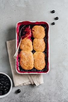 Zapatero de frambuesas y grosellas negras con helado de frambuesa en una fuente para hornear. pasteles caseros de tarta de frutas. fondo vintage gris. vista superior.
