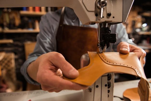 Zapatero hombre cosiendo piezas de cuero