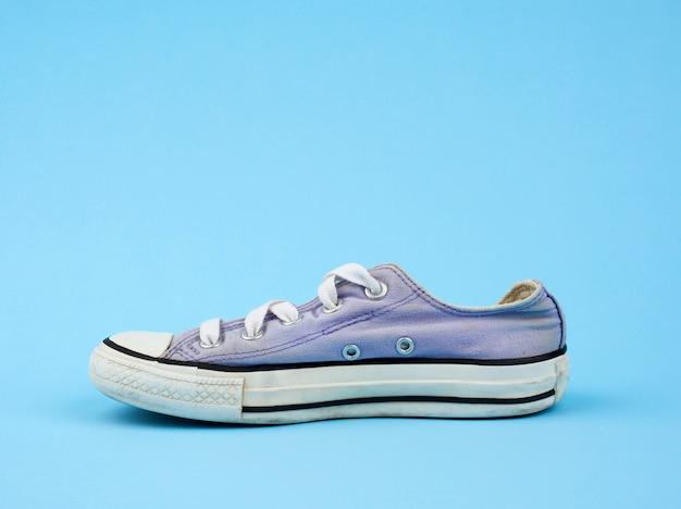 Zapatilla deportiva desgastada de color púrpura con cordones