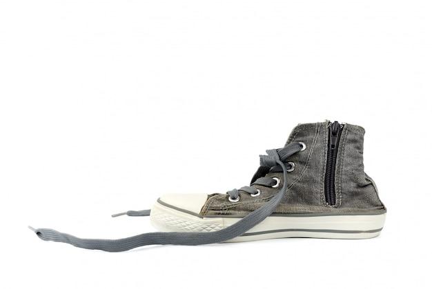 Zapatilla deportiva gris con cordones textiles desatados