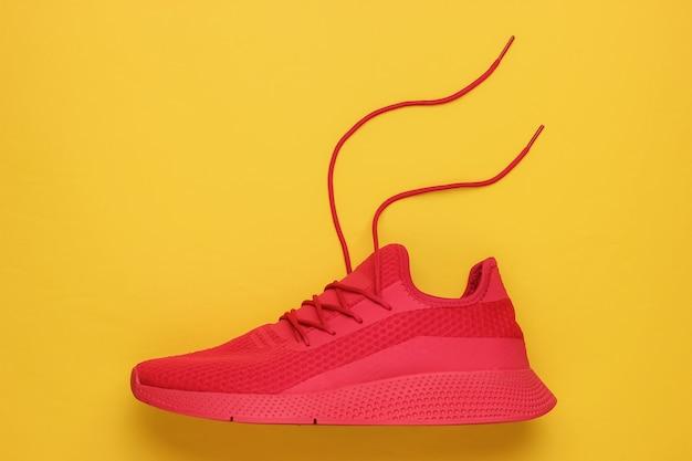 Zapatilla deportiva roja con cordones desatados sobre fondo amarillo